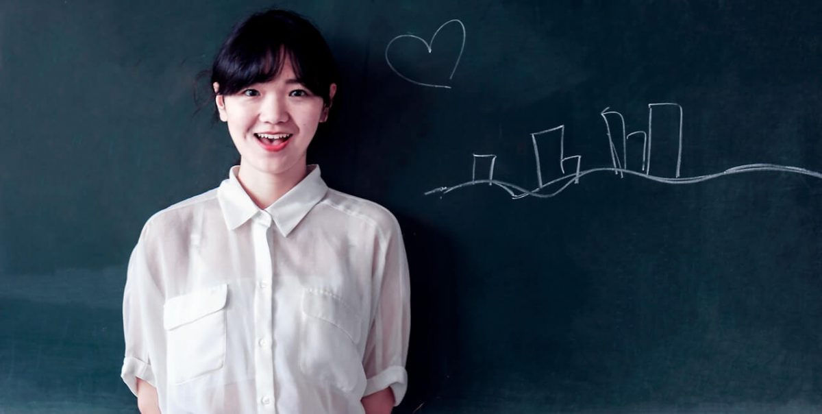 Dziewczyna-usmiecha-sie-na-tle-tablicy